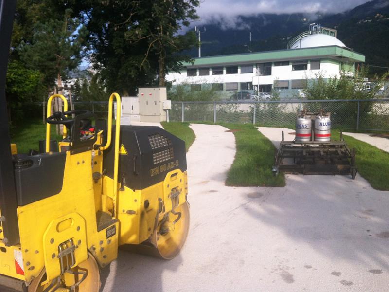 Entfernen von Abdrücken in der Farbasphaltfläche verursacht durch die Stempel eines LKW Kranwagens in Innsbruck (Innpromenade)