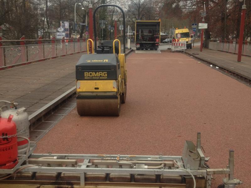 Nacharbeiten einer Arbeitsfuge in einer roten Gussasphaltfläche auf der Tiergartenbrücke in München.