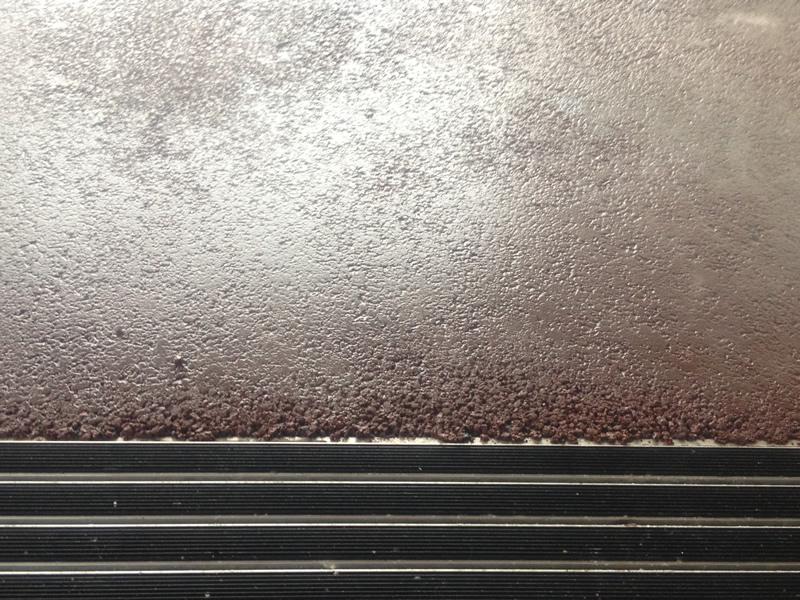 Angleichen von einer roten Farbasphaltdeckschicht an der Musikhochschule in Salzburg.